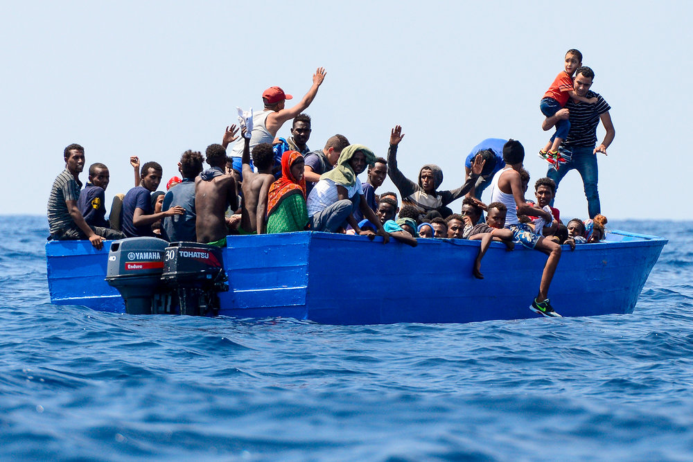 Migrants on a wooden boat react as they wait to be rescued by SOS Mediterranee organisation and Doctors Without Borders during a search and rescue (SAR) operation with the MV Aquarius rescue ship in the Mediterranean Sea, off the Libyan Coast, August 10, 2018.