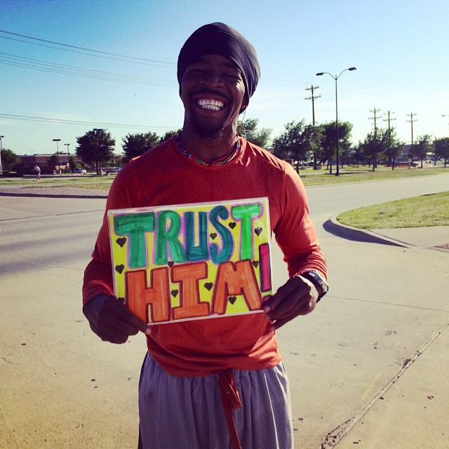 "Jimmy Lee holding a handmade sign that says, ""TRUST HIM!"""