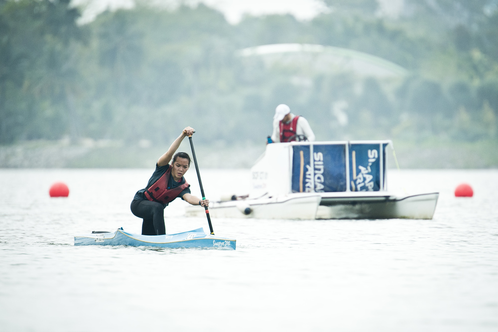 A canoeist paddles past a speed boat during training at the Marina Channel.
