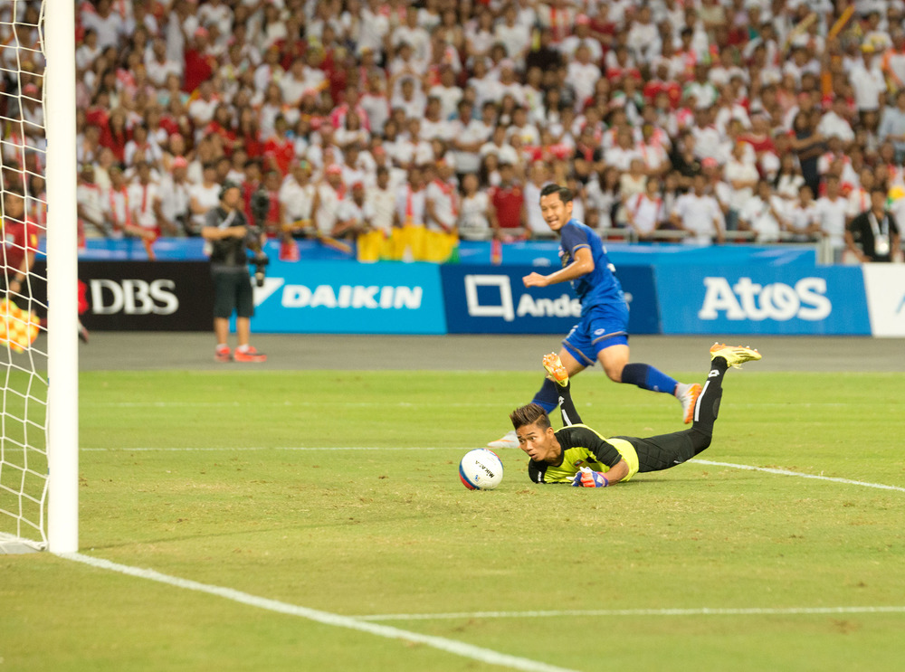A Burmese goal keeper watches as the ball enters goal during the SEA Games at the National Stadium.