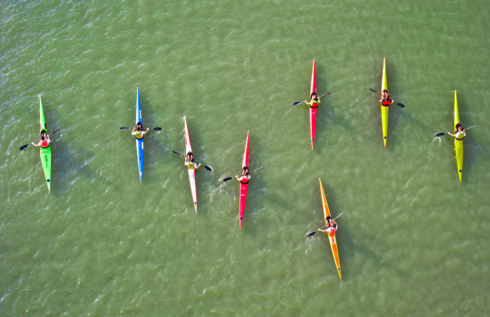Kayaks paddle through the algae bloom at the Marina Channel.