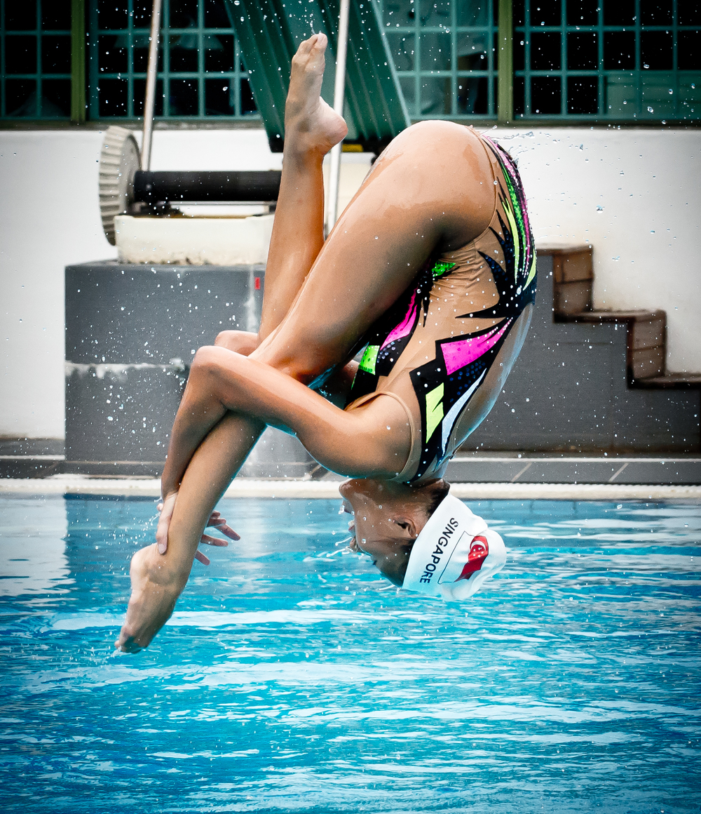 A synchronised swimmer is lifted into the air during the Schools Nationals at the Toa Payoh Swimming Complex.