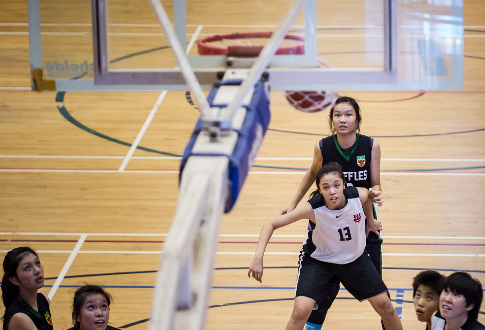 Basketball players watch as the ball makes the basket during a National Schools match at the Jurong East Sports Complex.