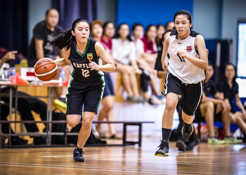 A Basketball player drives with the ball during a National Schools match at the Jurong East Sports Complex.