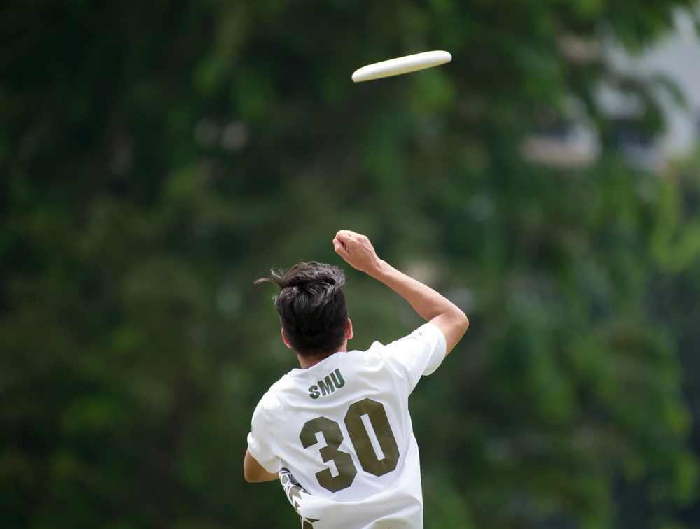 A player jumps to receive the frisbee during a friendly at Ang Mo Kio Central.