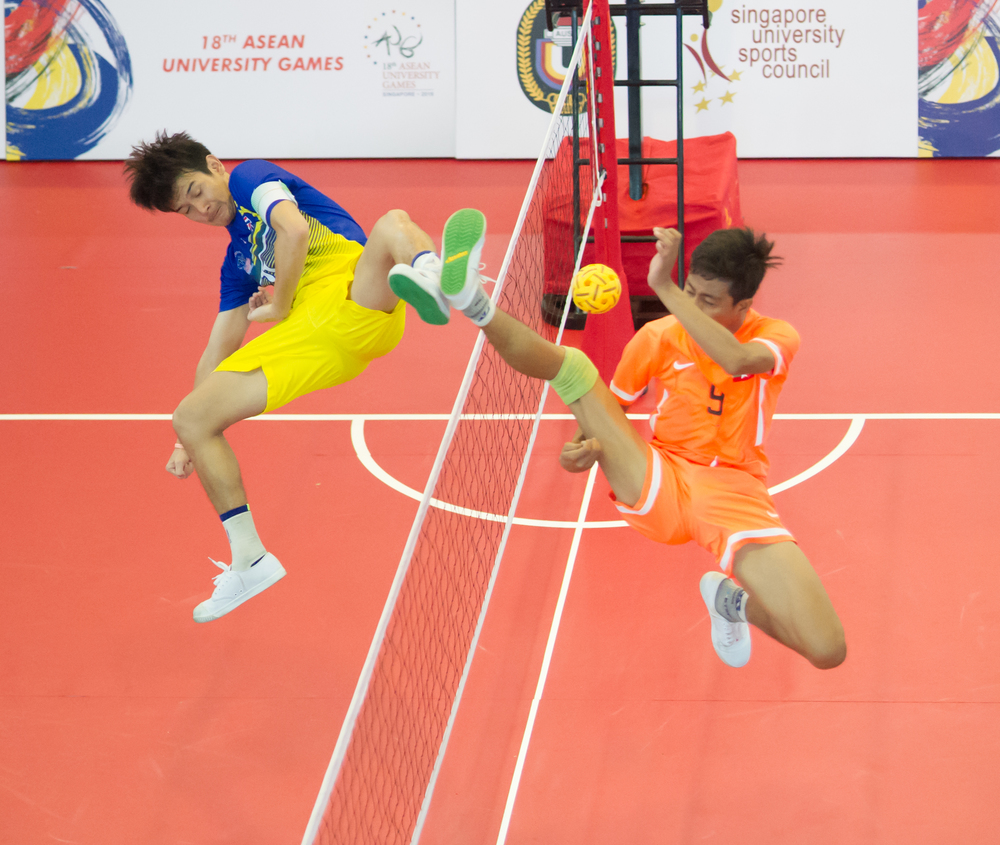 A Thai and Myanmar player in action during the sepak takraw competition of the ASEAN University Games at the Bedok Sports Hall.