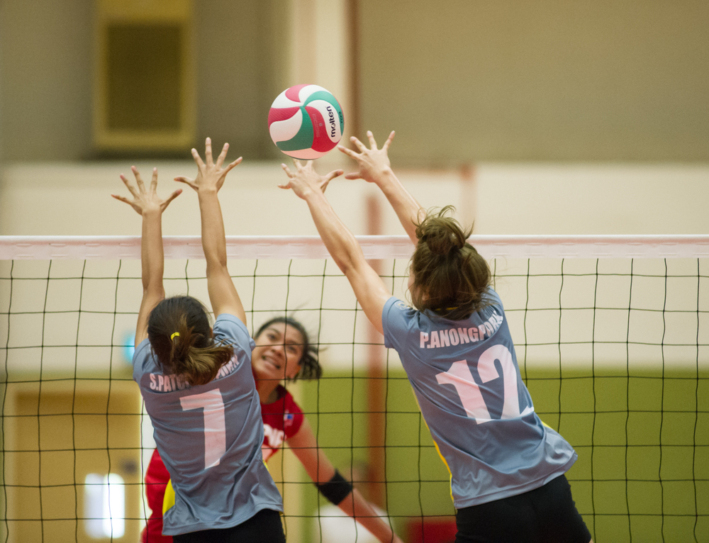 A Filipino player spikes past two Thai players during the volleyball competition of the ASEAN University Games at the National University of Singapore