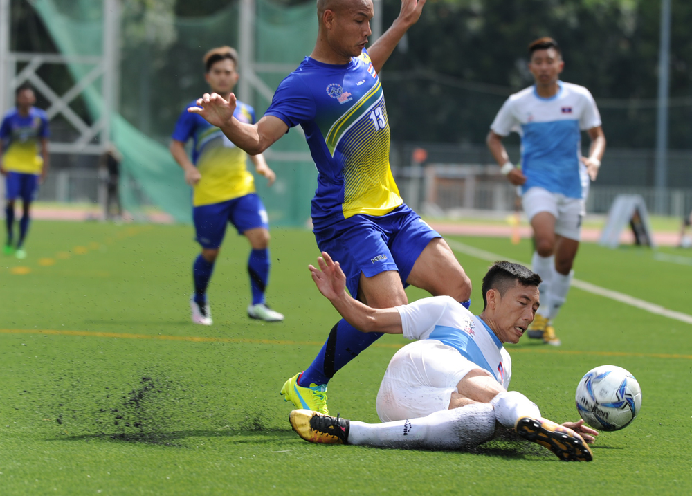 A Laotian player tackles a Thai player during the soccer competition of the ASEAN University Games at the Nanyang Technological University.