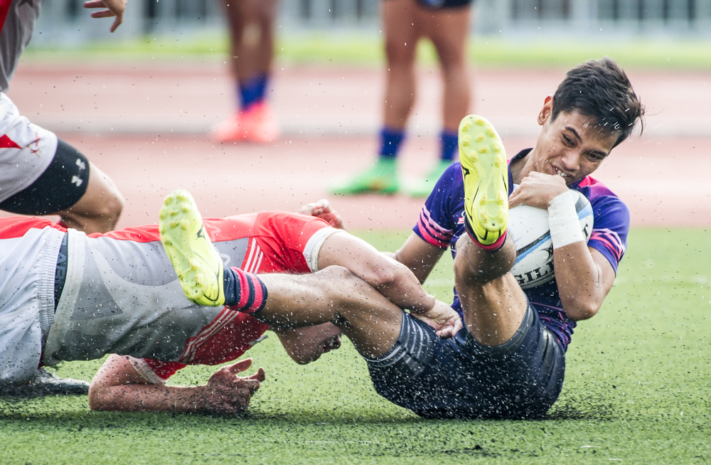 A Singaporean player tackles a Malaysian player during the rugby competition of the ASEAN University Games at the Nanyang Technological University.
