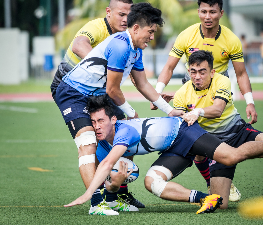 A Laotian player is tackled during the rugby competition of the ASEAN University Games at the Nanyang Technological University.