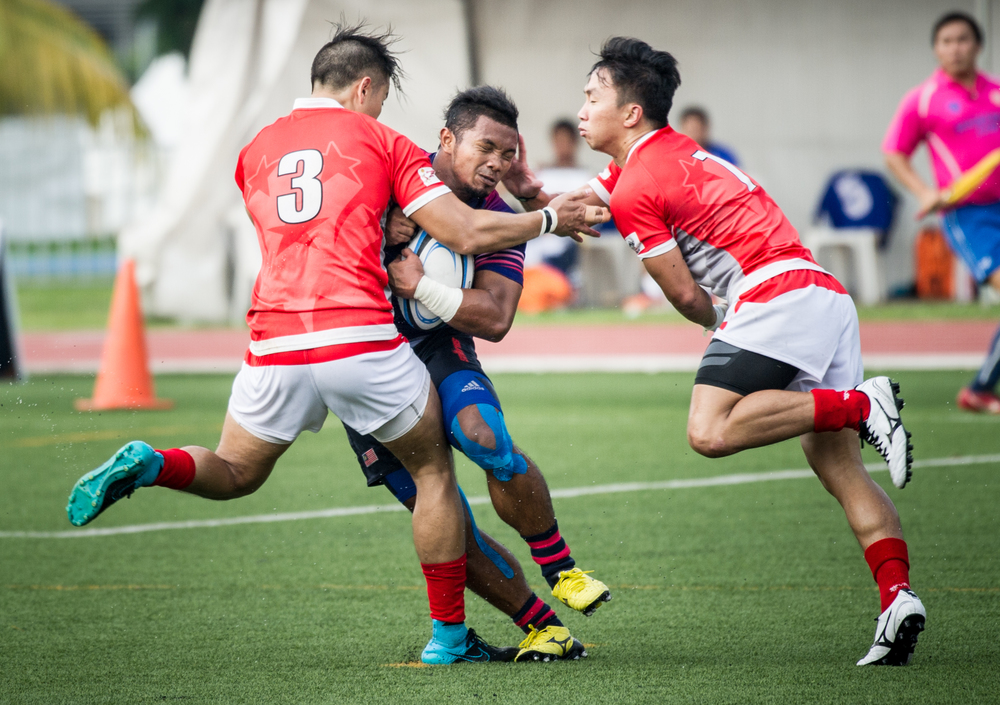 Two Singaporean players attempt to tackle a Malaysian player during the rugby competition of the ASEAN University Games at the Nanyang Technological University.