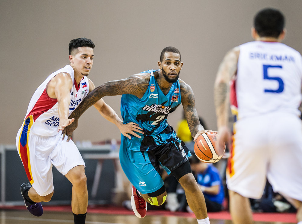 A Malaysian Basketball player drives pass a Phillipines player during the Merlion Cup basketball competition at the OCBC Arena.