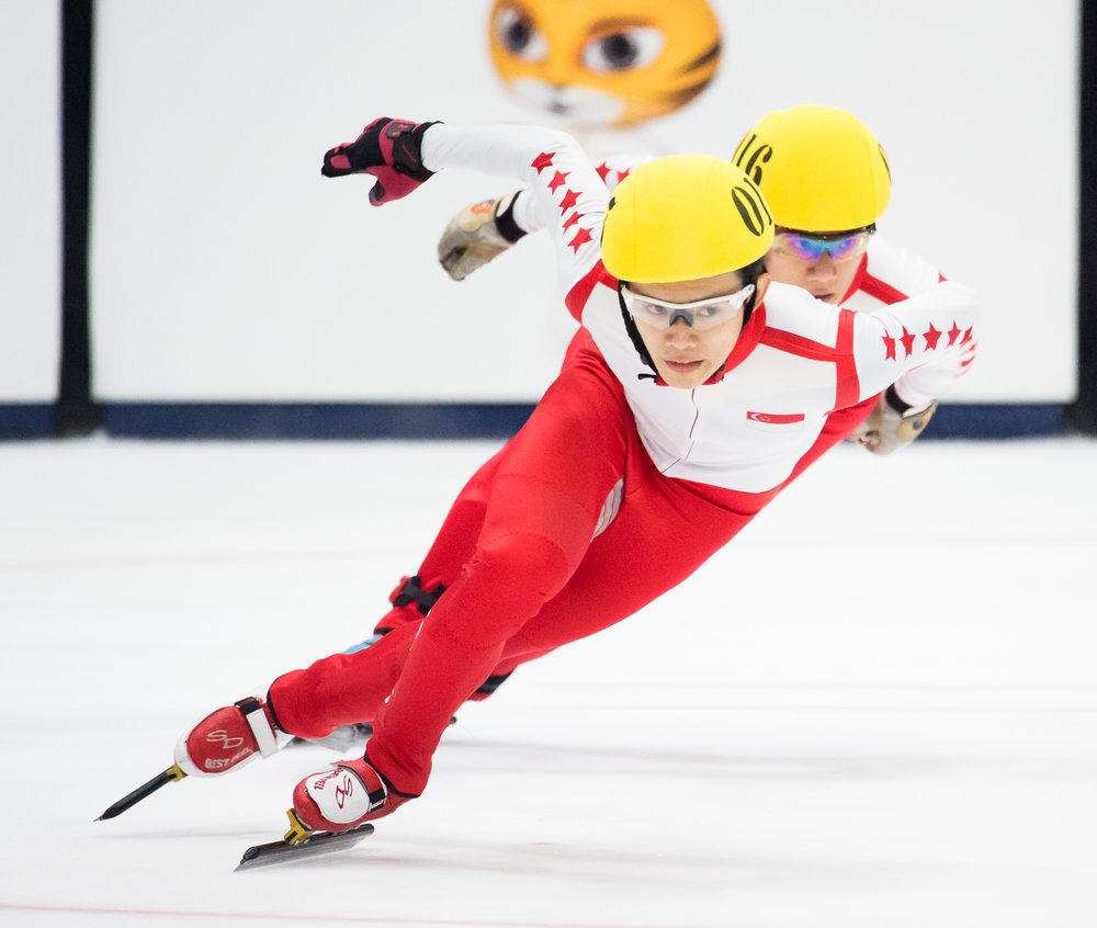 Two Singaporean speed skaters in action during the SEA Games at the Empire City Skating Rink.