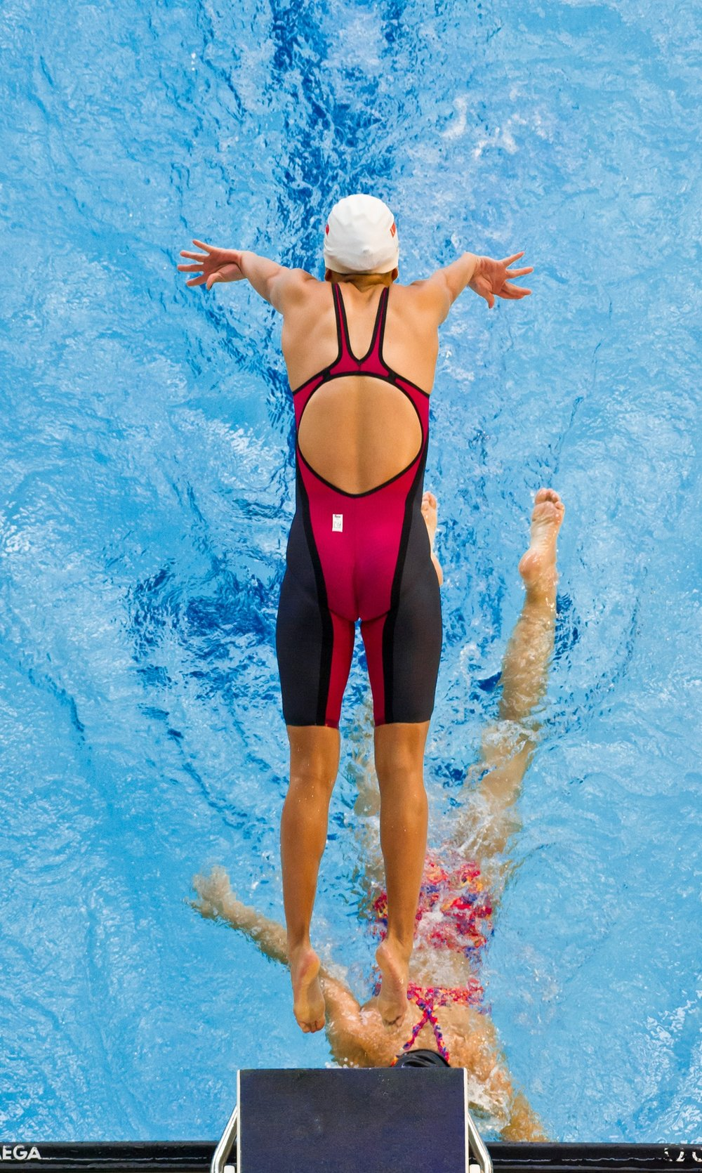 A swimmer dives in during a relay at the IVP finals at the Singapore Sports School.