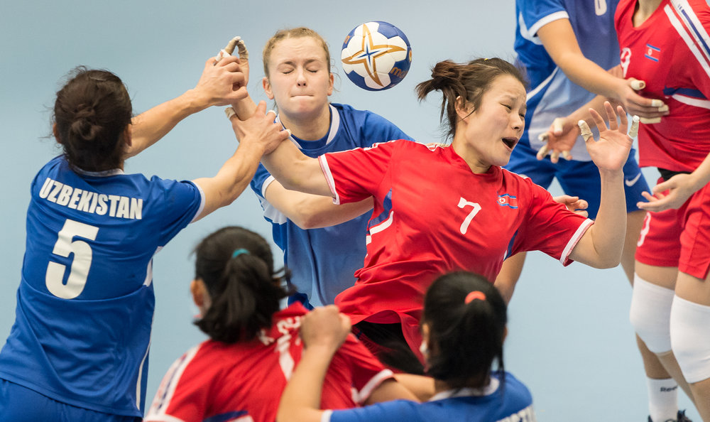 Uzbek players grab a North Korean player's arm during an International hand ball match at Our Tampines Hub.