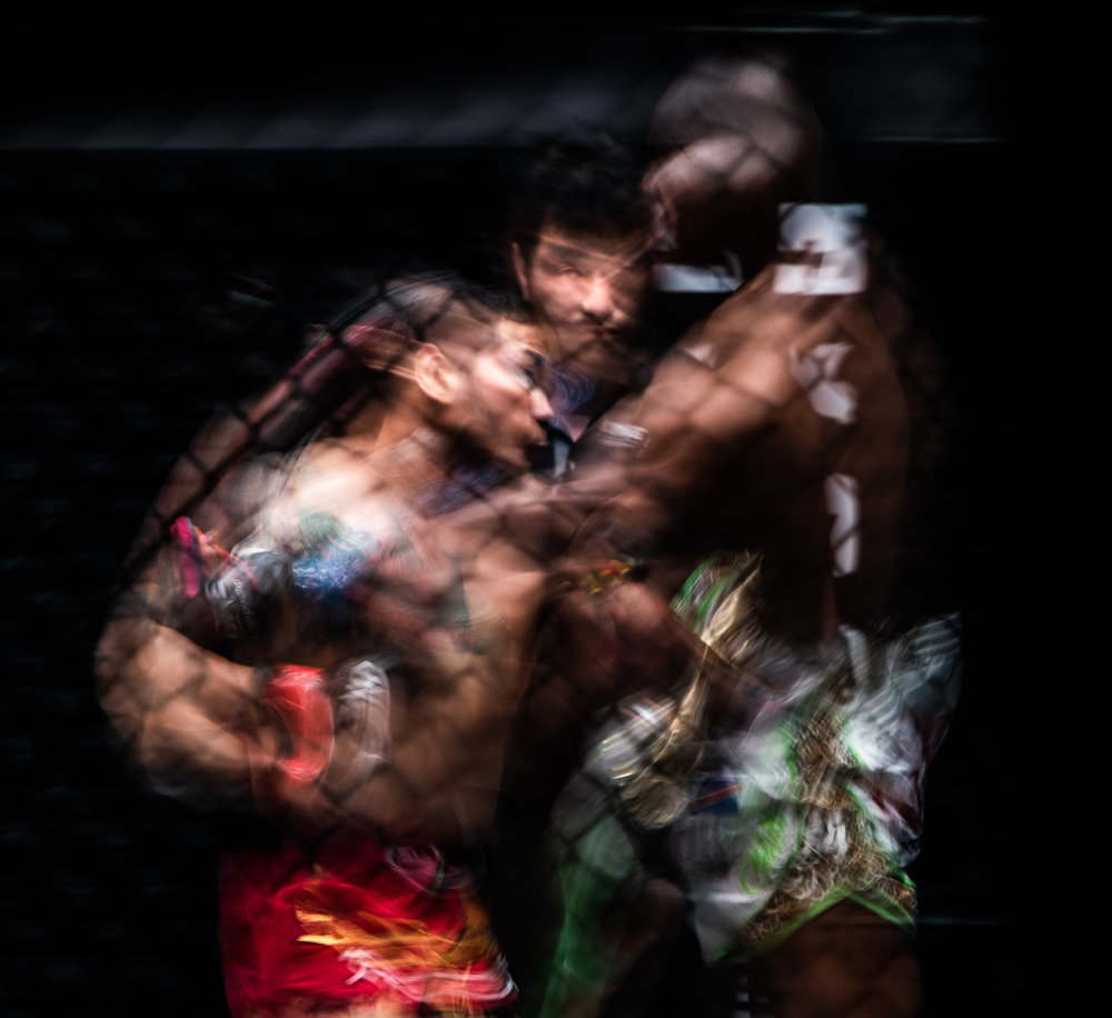 Thai and Congolese kickboxers exchange blows as the referee watches on during a One Championship World Title match at the Singapore Indoor Stadium.