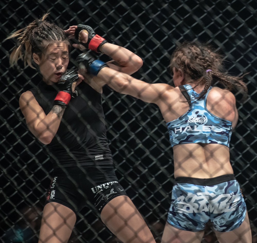A Japanese MMA athlete punches her Singapore opponent during a One Championship World Title match at the Singapore Indoor Stadium.