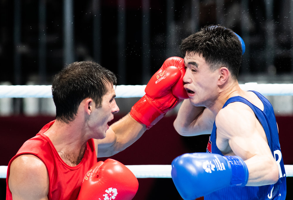 A Turkmenistan boxer punches his North Korean opponent during the Bantam Weight match of the Asian Games at the Jakarta International Expo.