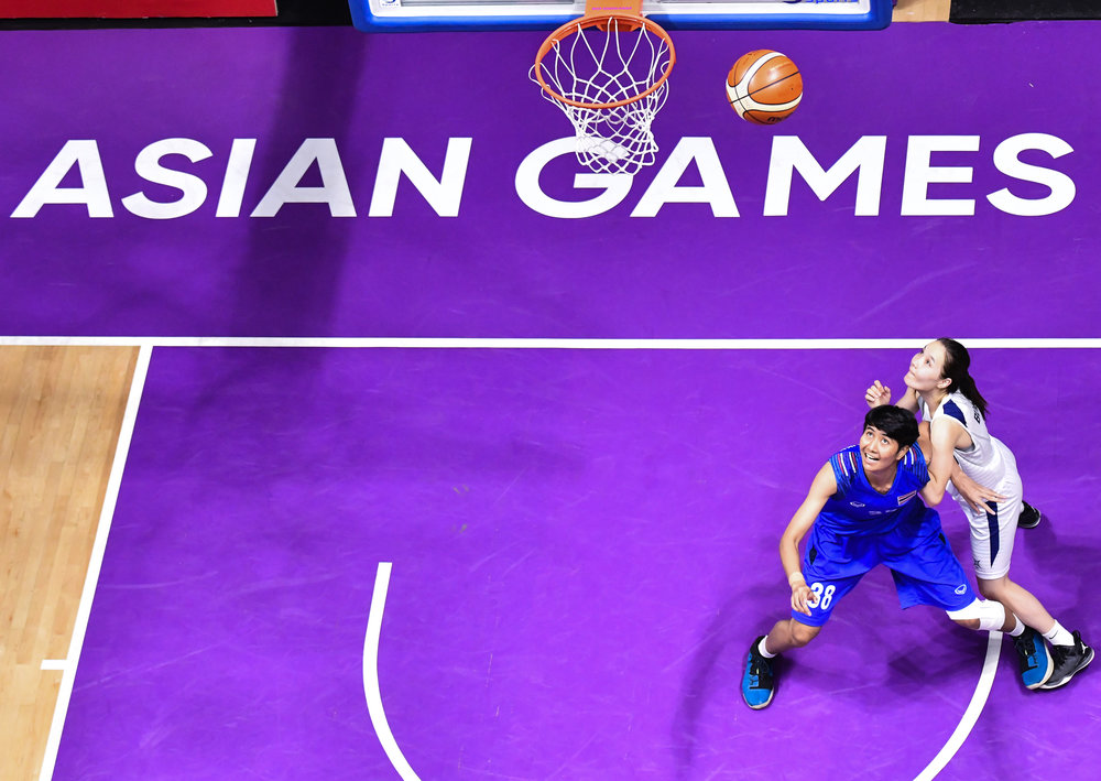 Thai and Mongolian players watch the ball rebound during a match of the Asian Games at the Gelora Bung Karno Sports Complex.