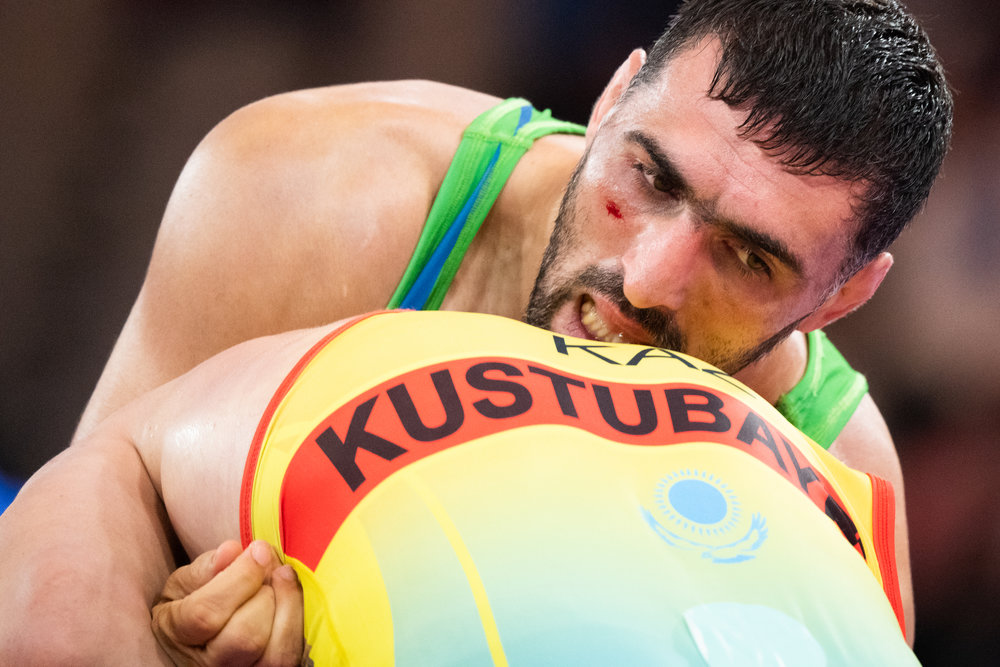 A Uzbek wrestler in action against his Kazakh opponent during his Greco Roman 87 kg match of the Asian Games at the Jakarta Convention Centre.