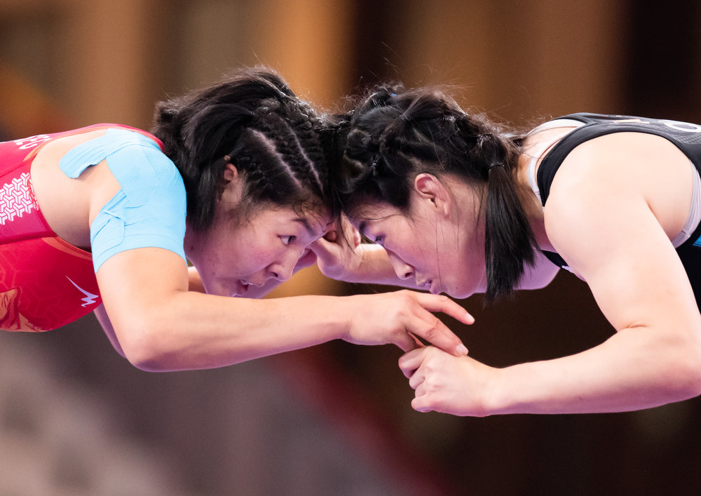 Chinese and Mongolian wrestlers face off during the women's 68kg freestyle finals of the Asian Games  at the Jakarta Convention Centre.