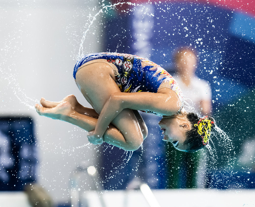 A Macau Swimmer spins through the air during the free routine of the Asian Games at the GBK Aquatic Centre.