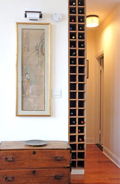 Thin floor-to-ceiling wine tower built into wasted space in a hallway.