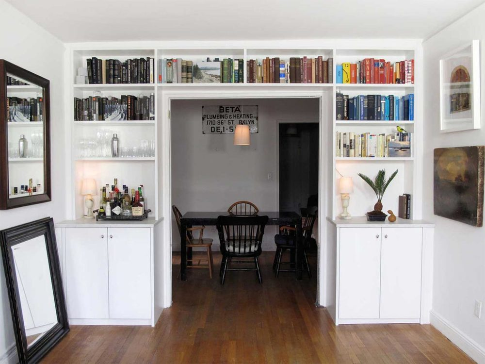 Built-in bookshelves frame the entryway to the dining room, and were incorporated seamlessly with a marble-top bar.