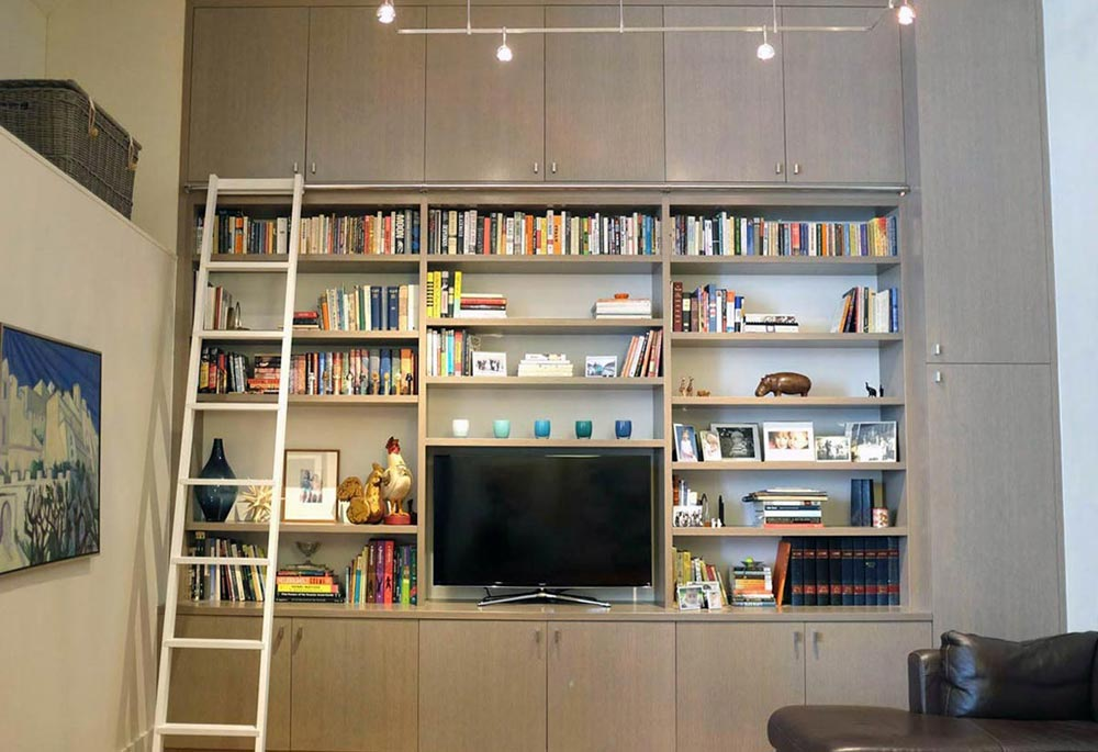 Tall rift white oak bookshelves and cabinets with ladder.