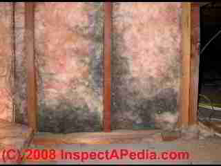 Accumulated dirt on fiberglass batts due to air leakage through the wall assembly.