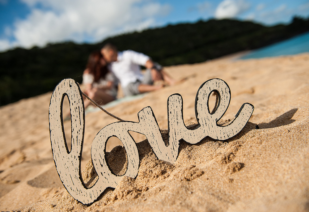 Love sign on the beach with engaged couple in the background