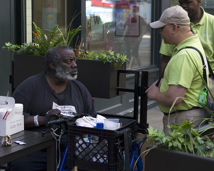 "(Above) A homeless Chicagoan outside a fast food restaurant on State Street talks with two members of a Chicago Loop Alliance ""Street Team."""