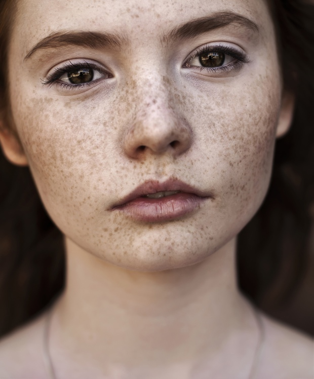 Portrait of a beautiful brunette with freckles