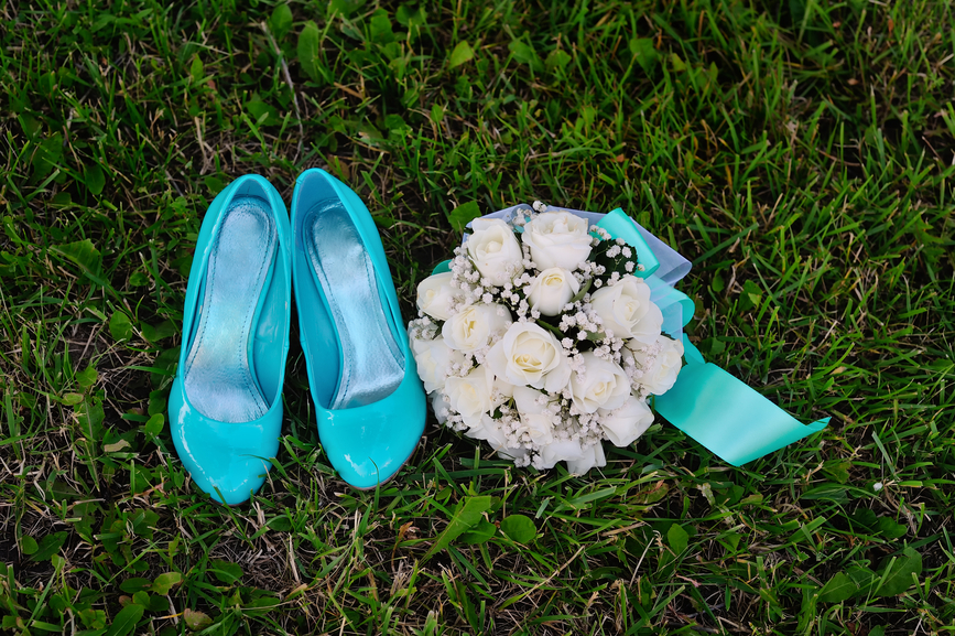 bridal bouquet and turquoise shoes on green grass