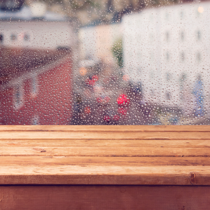 Empty wooden deck table over window with rain drops. Ready for product montage display