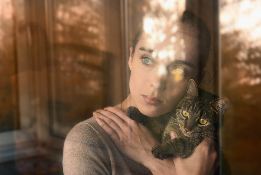attractive girl holding a cat and sits by the window