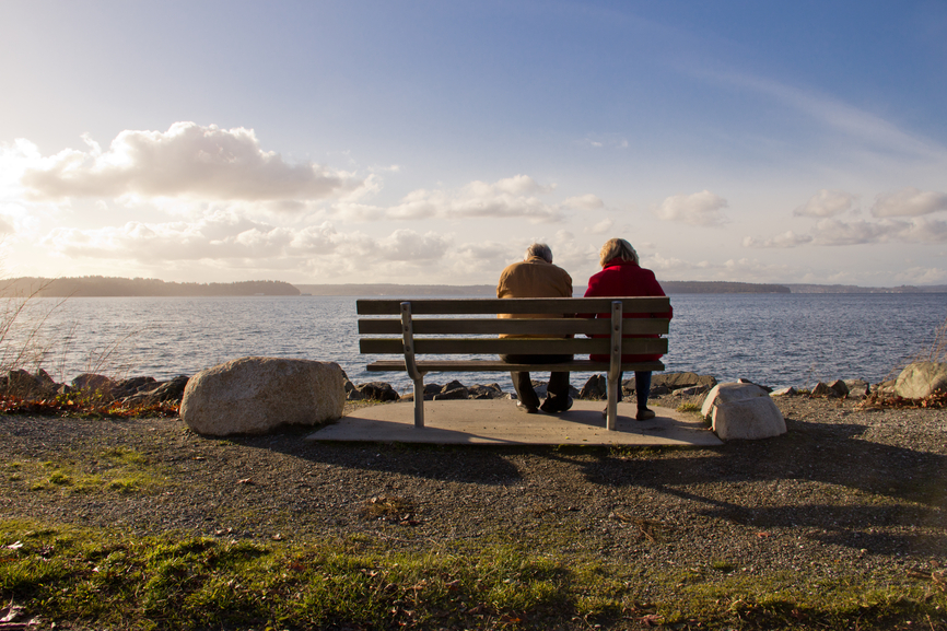 Elderly Couple Relaxing Together on Park Bench Facing a Lake