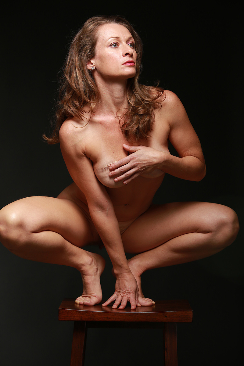Nude art model sitting clearly