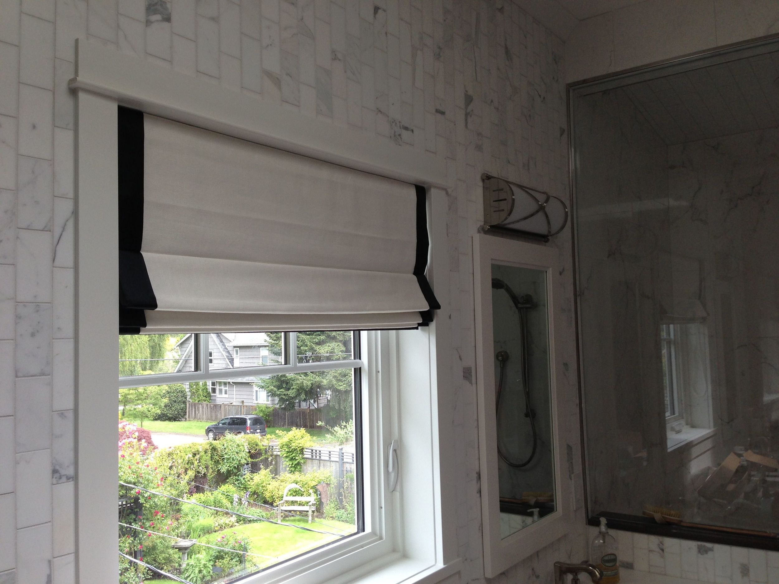 The Master Bathroom has the same roman valance treatment, Classic Chic, but it sets off the calacutta tile and the Robert Abbey lighting nicely.