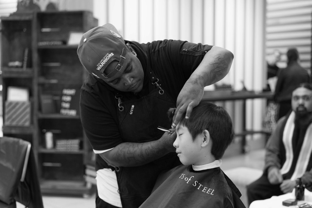 Tee, barber @ San Francisco Barbershop, giving a Saint One, Support One haircut to Lawrence at the Saints of Steel pop-up charity barbershop @ Westfield San Francisco Centre's Bespoke Demo. Photo by Ryan Anthony