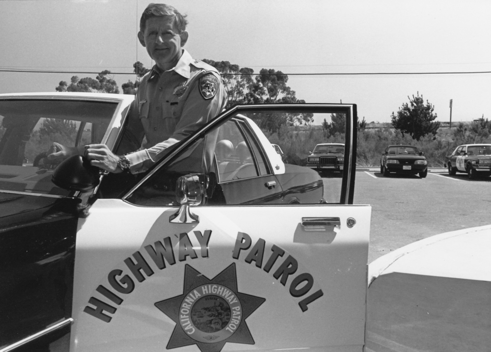 Officer Tom Campbell poses by his California Highway Patrol car during the 1980's