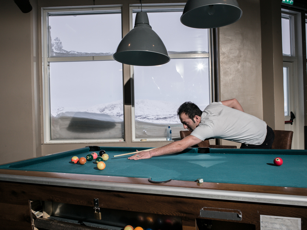 Riksgränsen, Sweden. February 2nd, 2016. Daniel, from Afghanistan, enjoys a game of pool billiards. Along with the gym, this is a popular pastime.