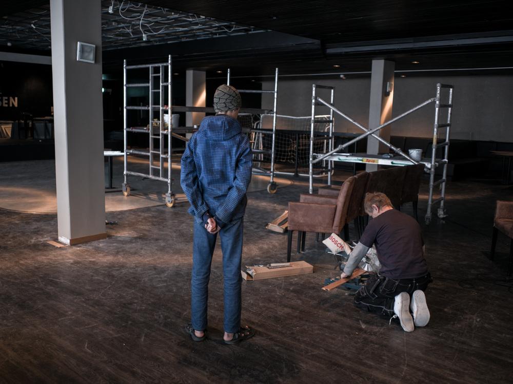 Riksgränsen, Sweden. February 2nd, 2016. An older child observes a Swedish carpenter who is working on some refurbishement.