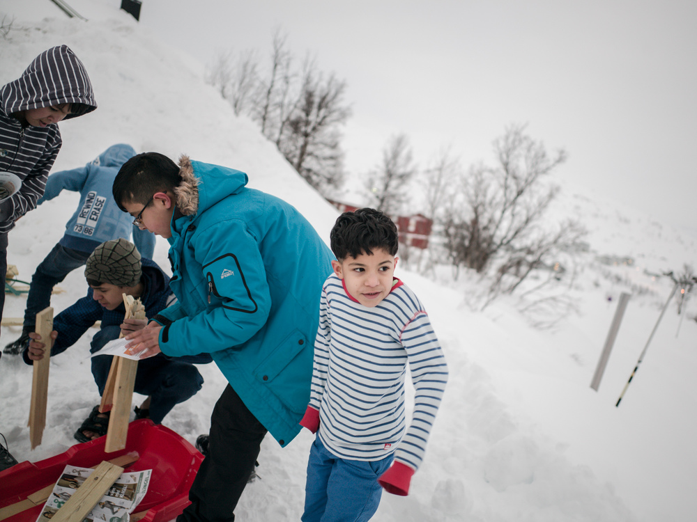 Riksgränsen, Sweden. February 2nd, 2016. This group of children, with weather permitting, like to create two bonfires a day. They have created a system of storing and transporting wood. The weather is a bit milder this time of the month and some brave the weather without jacket.
