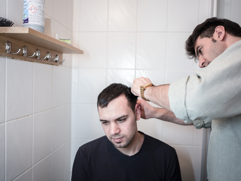 Riksgränsen, Sweden. February 2nd, 2016. Mehdi, from Iran, has become the resident barber. He is cutting Maed's hair today for a small fee.