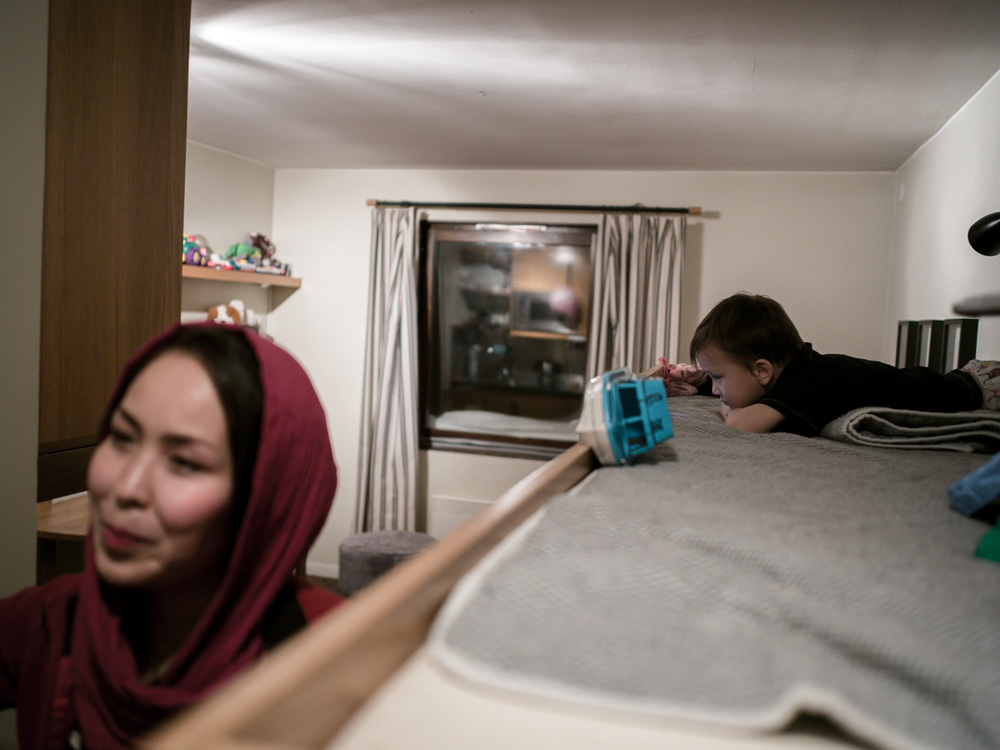 Riksgränsen, Sweden. February 2nd, 2016. Zakera says goodbye to her guests as her son, Taha, watches a British children's show on a smart phone.