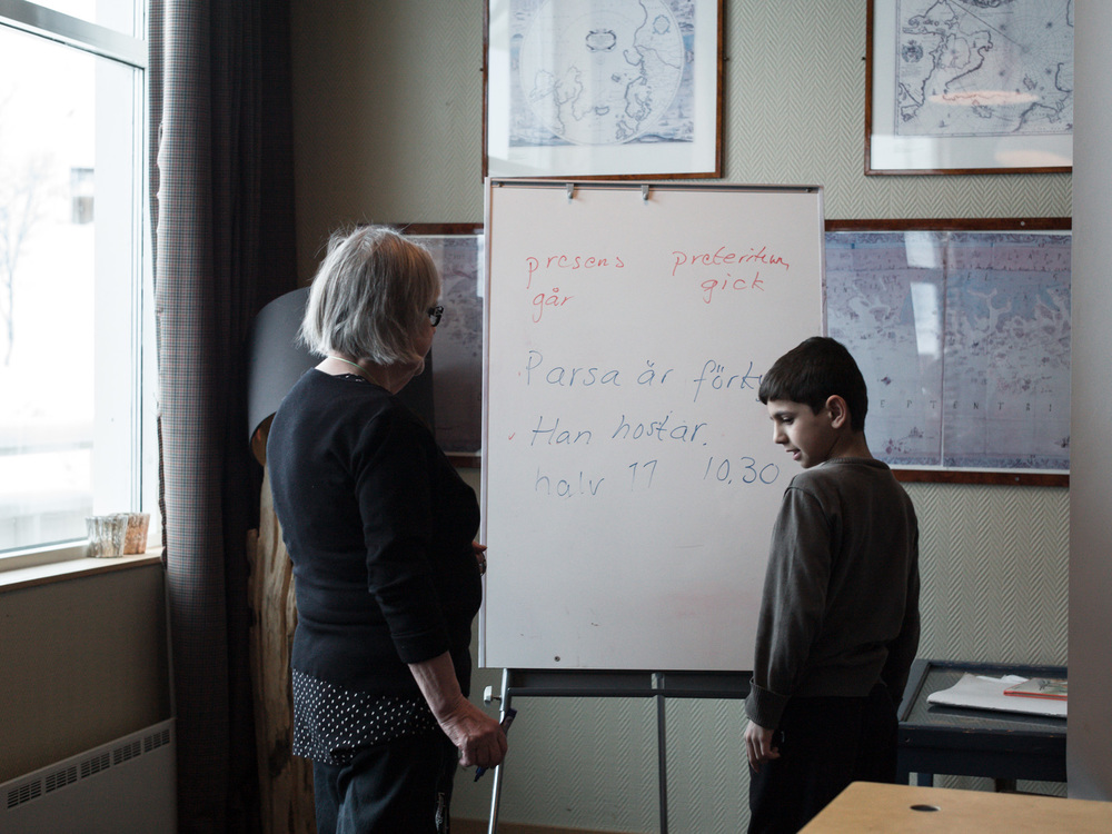 Riksgränsen, Sweden. February 3rd, 2016. Parsa, from Afghanistan, writes that he has a cold on the whiteboard. Gunn-Britt corrects him.