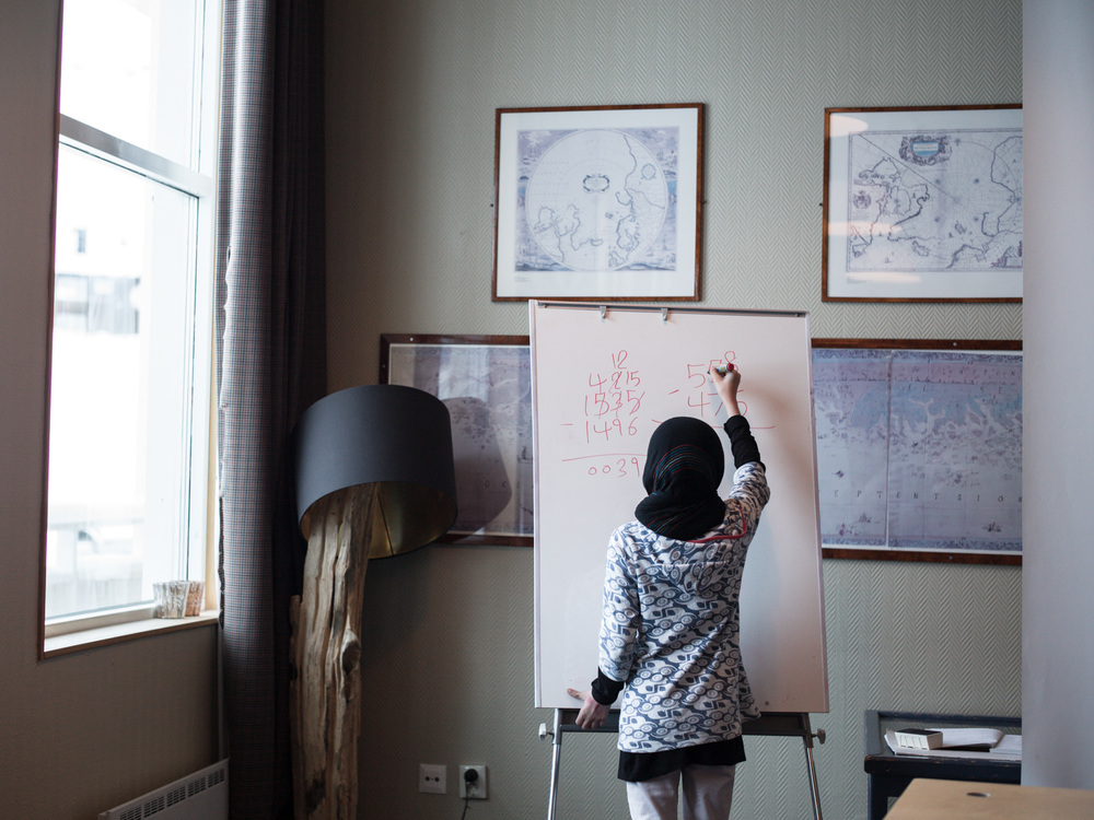 Riksgränsen, Sweden. February 3rd, 2016. A student solves an equation on the whiteboard. Arithmetic is the children's strongest subject. Sometimes there is confusion between teachers and students due to the use of different mathematical notation systems. Mathematics is the most common class as the teachers are not hindered by language barriers