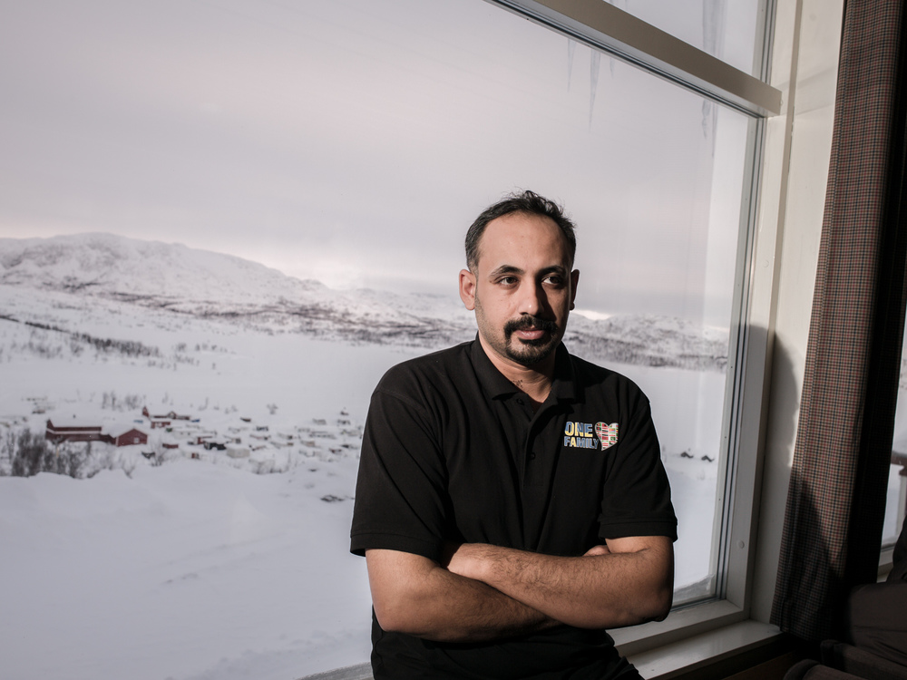 Riksgränsen, Sweden. February 2nd, 2016. Ali from Iraq at the lobby of the resort. He is wearing a T-shirt with the inscription 'One Family', a reference to the community that has been created at the resort. The snazzy logo contains a Swedish flag alongside the flags of all the nationalities represented a the temporary refugee lodging.