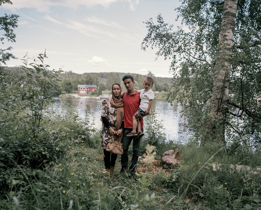 Torpshammar, Sweden. July 5th, 2016. Zakera, 24, Mahdi, 28, and their son Taha, 3, pose for a portrait at one of Mahdi's favourite fishing spots in the village of Viskan, Torpshammer. The family is from Afghanistan and was previously housed at a ski resort above Sweden's Arctic circle.
